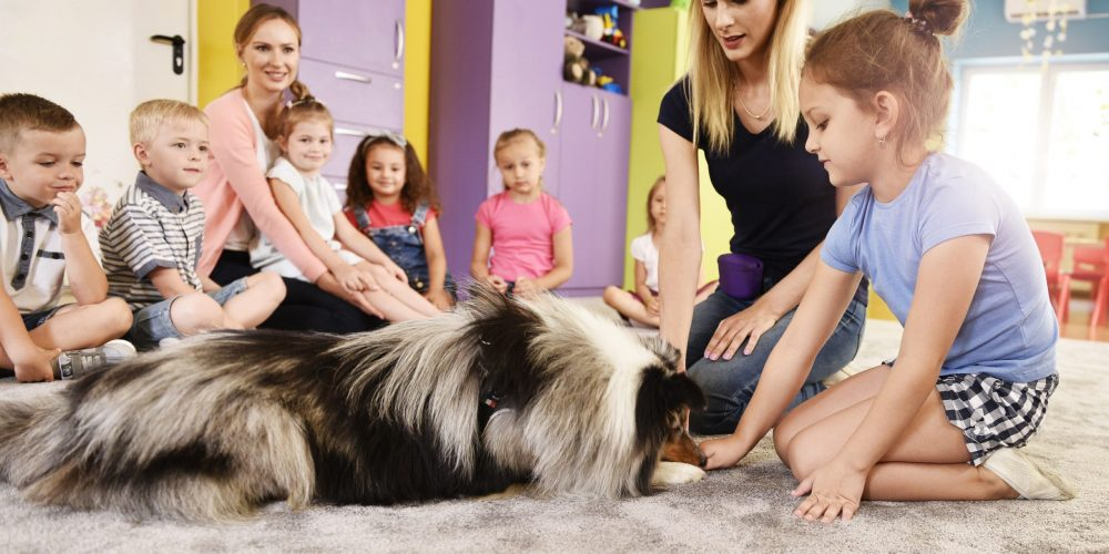 Woman and therapy dog working with kids in the preschool